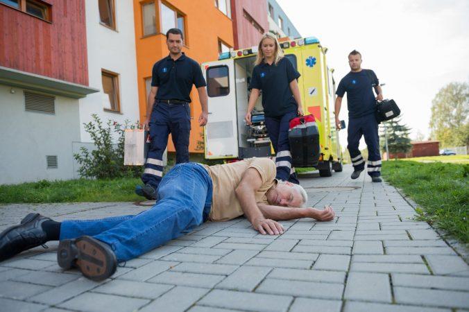 Paramedics giving help to injured senior man lying on street